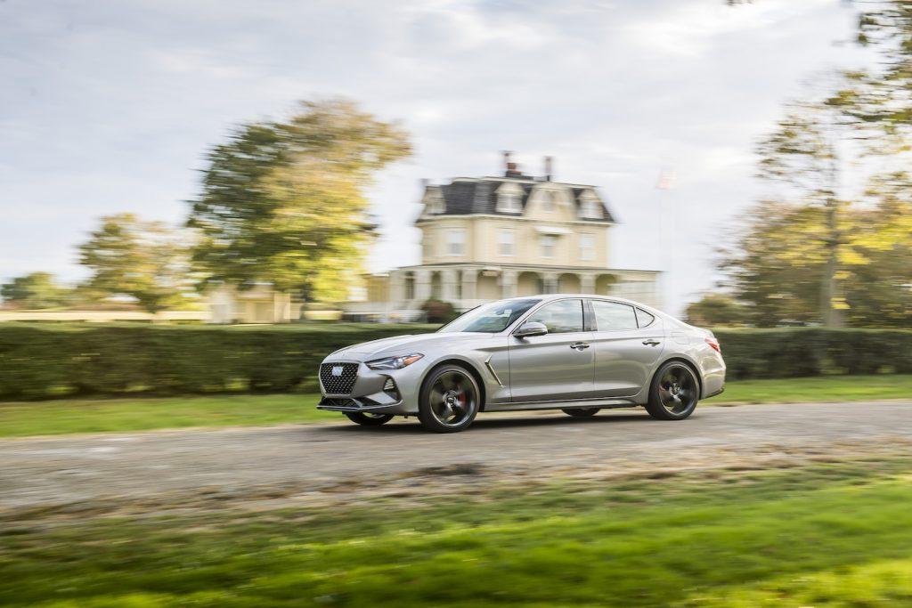 A silver 2021 Genesis G70 driving in a neighborhood, the 2021 Genesis G70 is an affordable luxury sedan