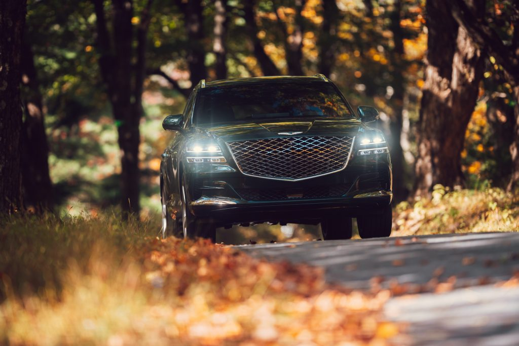 A head-on view of a dark-green 2021 Genesis GV80 luxury SUV with its headlights on in Hudson Valley, New York