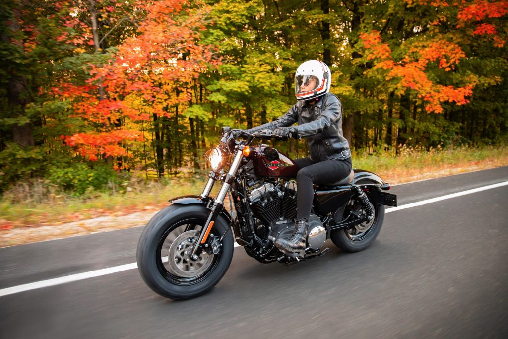 A rider rides a maroon 2021 Harley-Davidson Forty-Eight on a tree-lined road