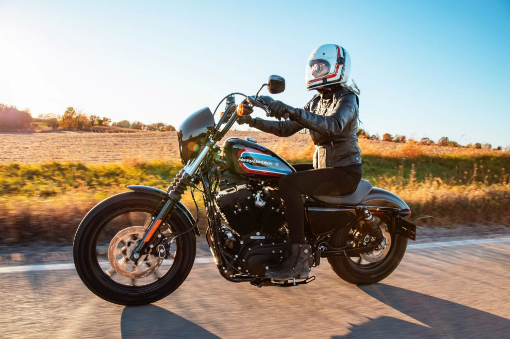 A white-helmeted, black-clad rider on a black 2021 Harley-Davidson Sportster Iron 1200 riding down the road