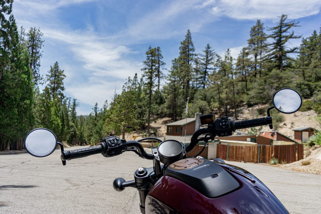 A maroon 2021 Harley-Davidson Sportster S handlebars with a view of the Angeles National Forest