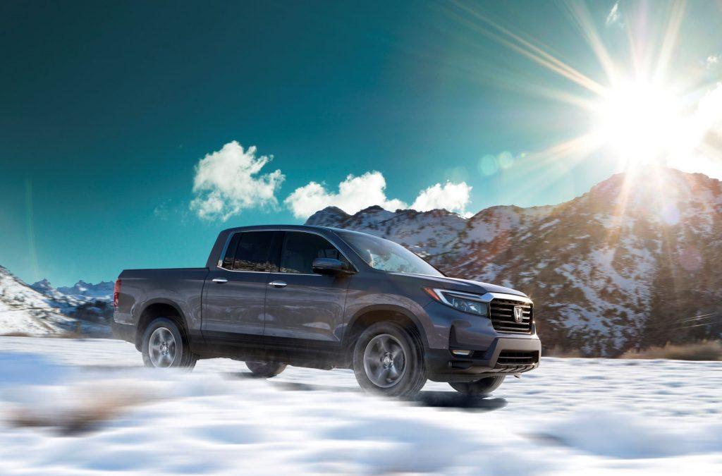The 2021 Honda Ridgeline RTL-E pickup truck model driving across a snowy plain as the sun rises over a mountain