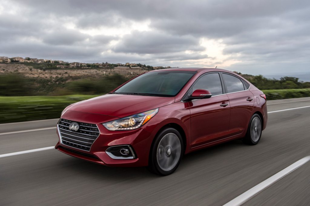 A red metallic 2021 Hyundai Accent traveling on a highway past green grass and hills on a cloudy day