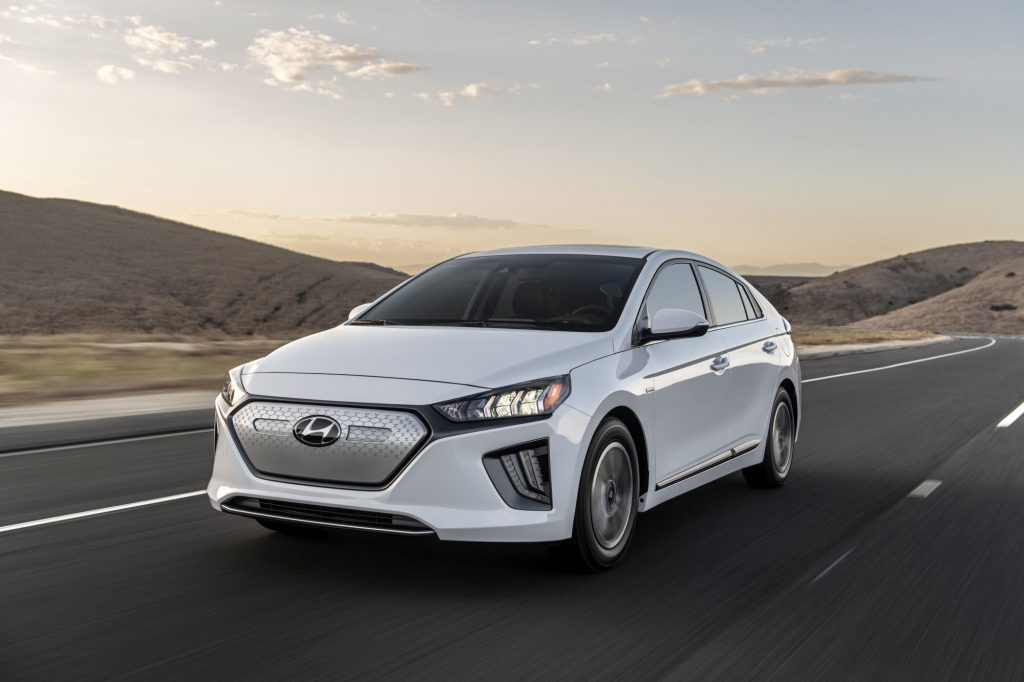 A white 2021 Hyundai Ioniq Electric sedan model driving on a highway