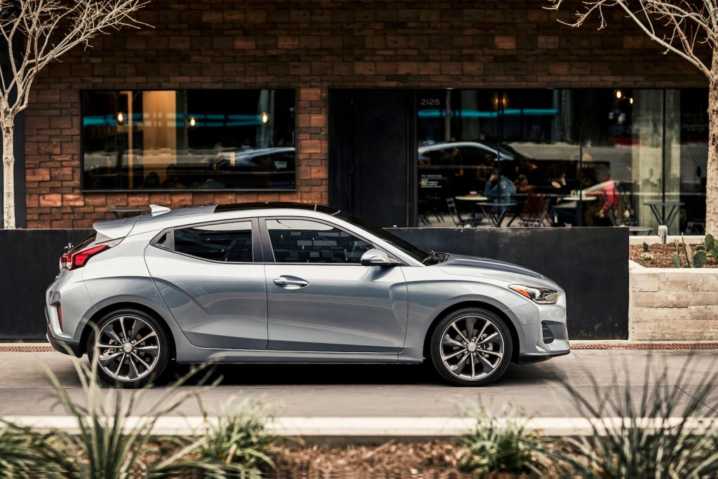 A silver 2021 Hyundai Veloster parked on the side of a street, the 2021 Hyundai Veloster is an affordable sporty new car under $40,000 recommended by Consumer Reports