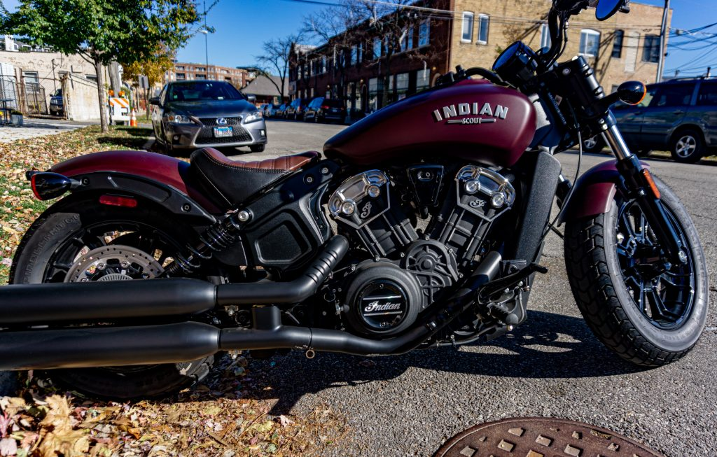 The side view of a maroon-and-black 2021 Indian Scout Bobber parked on the street