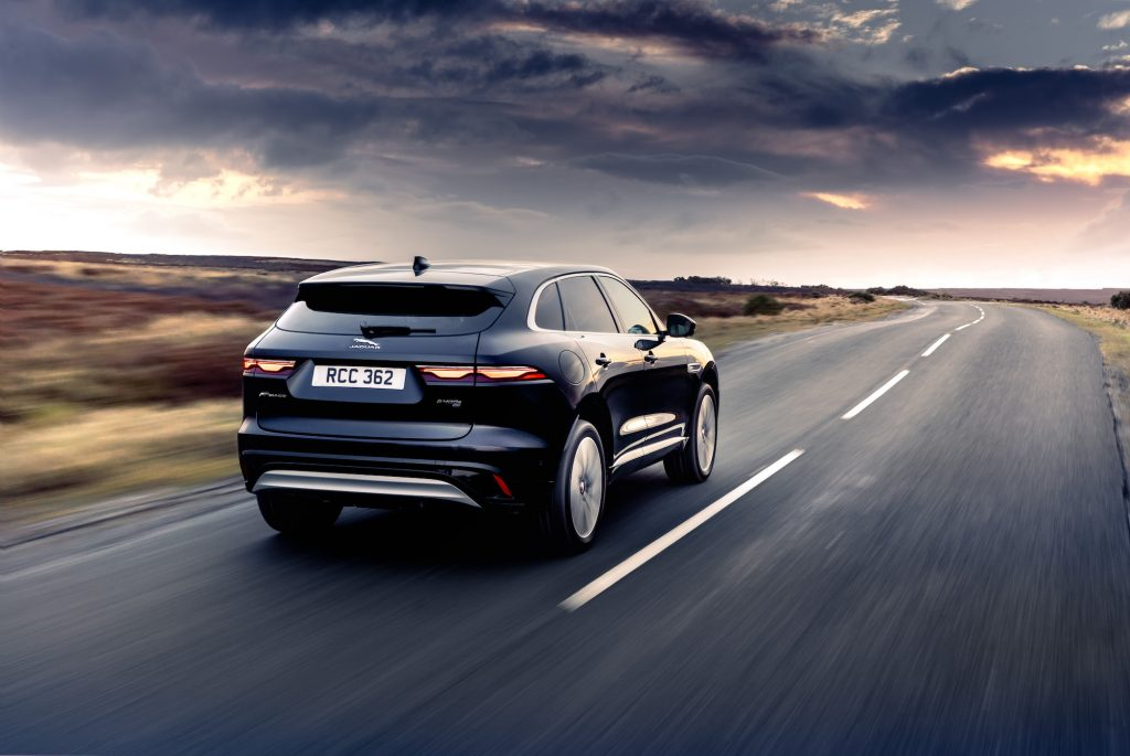 A dark-blue 2021 Jaguar F-Pace luxury compact SUV on a two-lane highway in the country as dark clouds form
