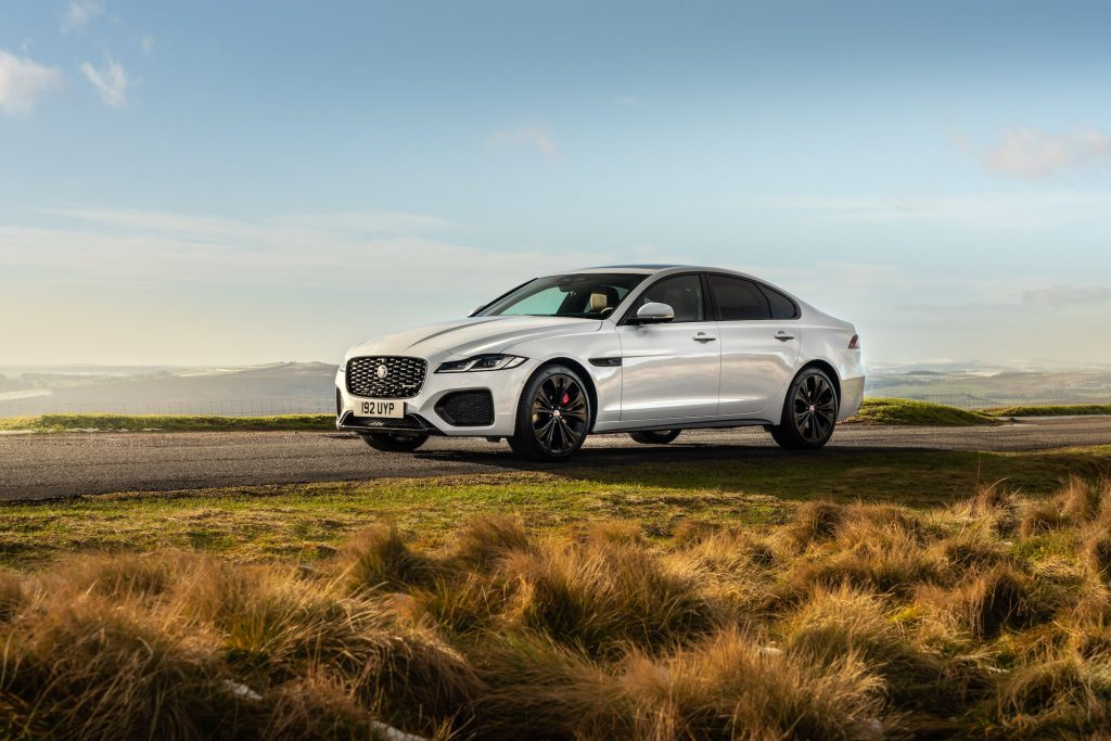 A white 2021 Jaguar XF luxury midsize sedan parked on a road overlooking mountains on a sunny day