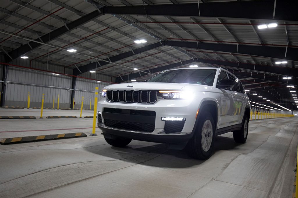 A white 2021 Jeep Grand Cherokee driving inside of a metal hanger building with a concrete floor.