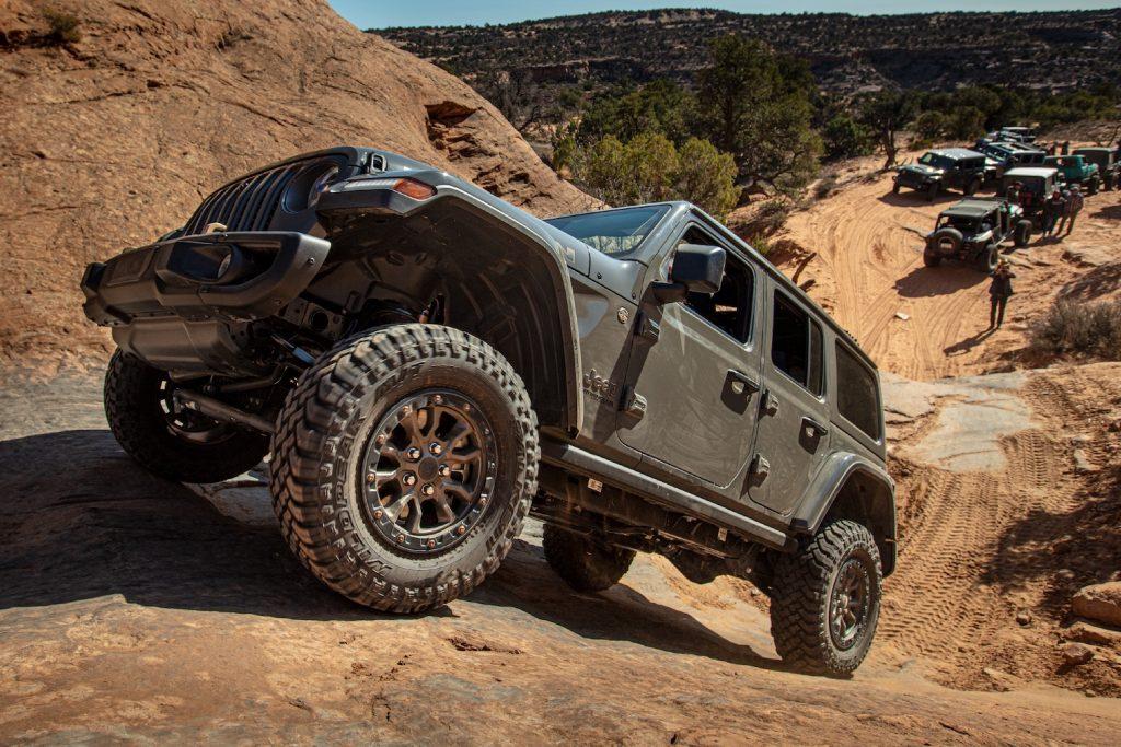 A grey 2021 Jeep® Wrangler Rubicon 392 climbing up a sandy hill
