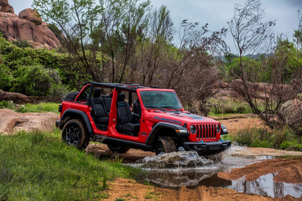 A red 2021 Jeep Wrangler Rubicon 4xe with no doors or roof splashes through a puddle on a desert trail