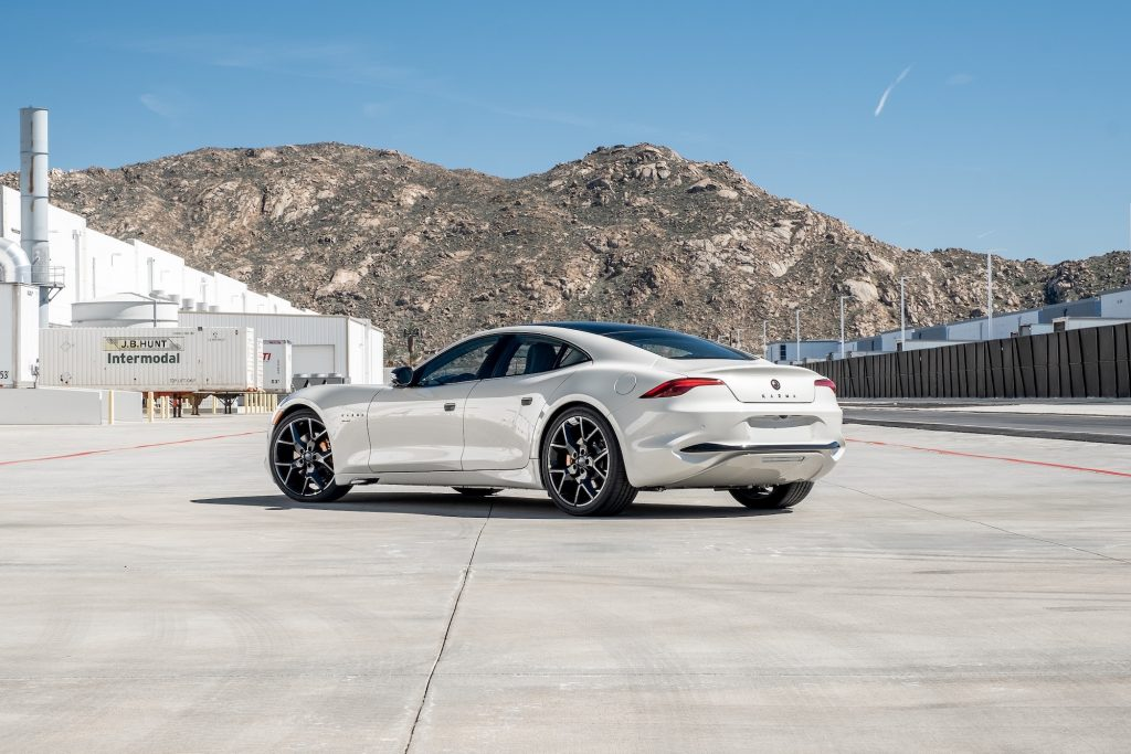 A white 2021 Karma GS-6 sports sedan parked outside a white warehouse in front of a mountain range on a sunny day