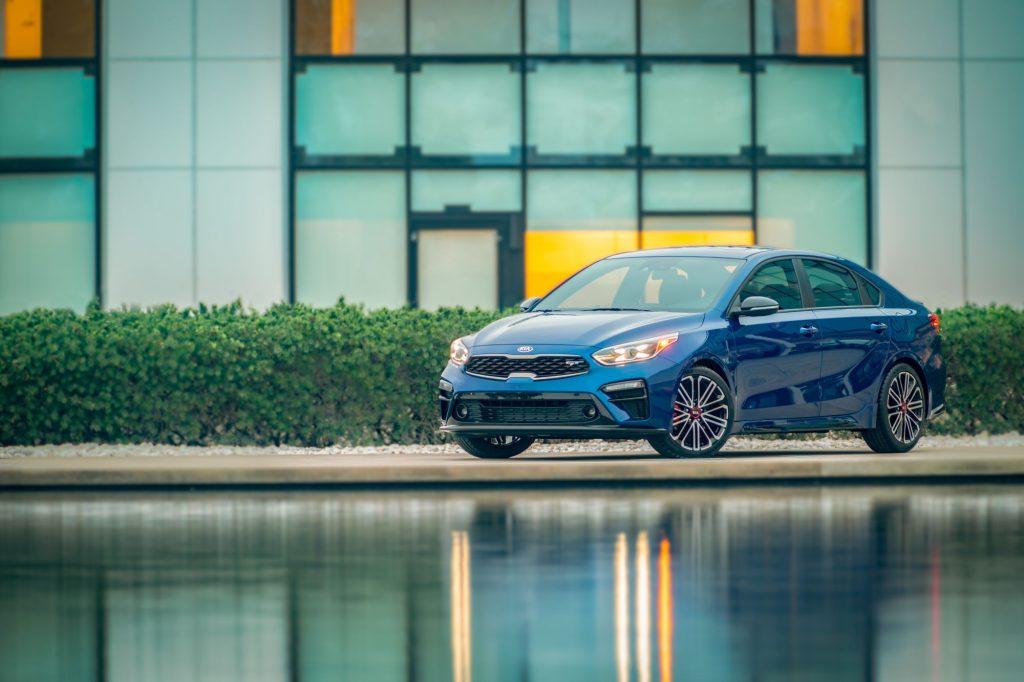 A blue 2021 Kia Forte GT Sport sedan model parked near a pond outside of a dealership