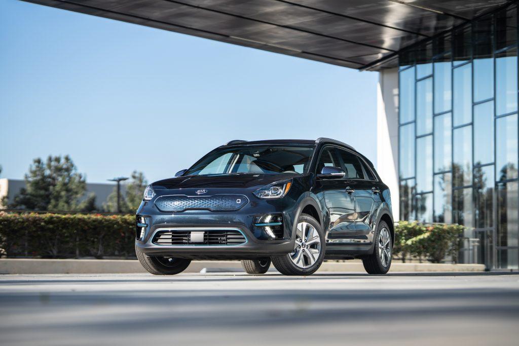 A dark-blue 2021 Kia Niro EV parked on concrete outside a modern glass building on a sunny day
