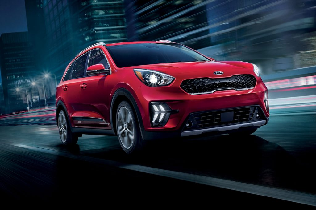 A red 2021 Kia Niro plug-in hybird compact SUV traveling on a wet city street at night