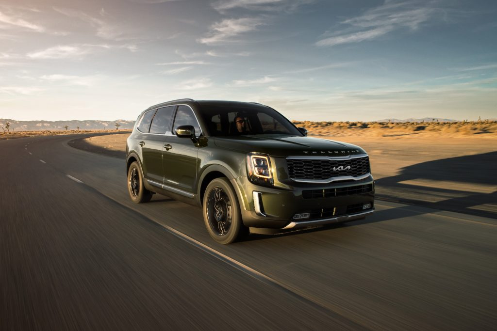 A green 2021 Kia Telluride driving down an empty road, the Telluride is a new three-row SUV