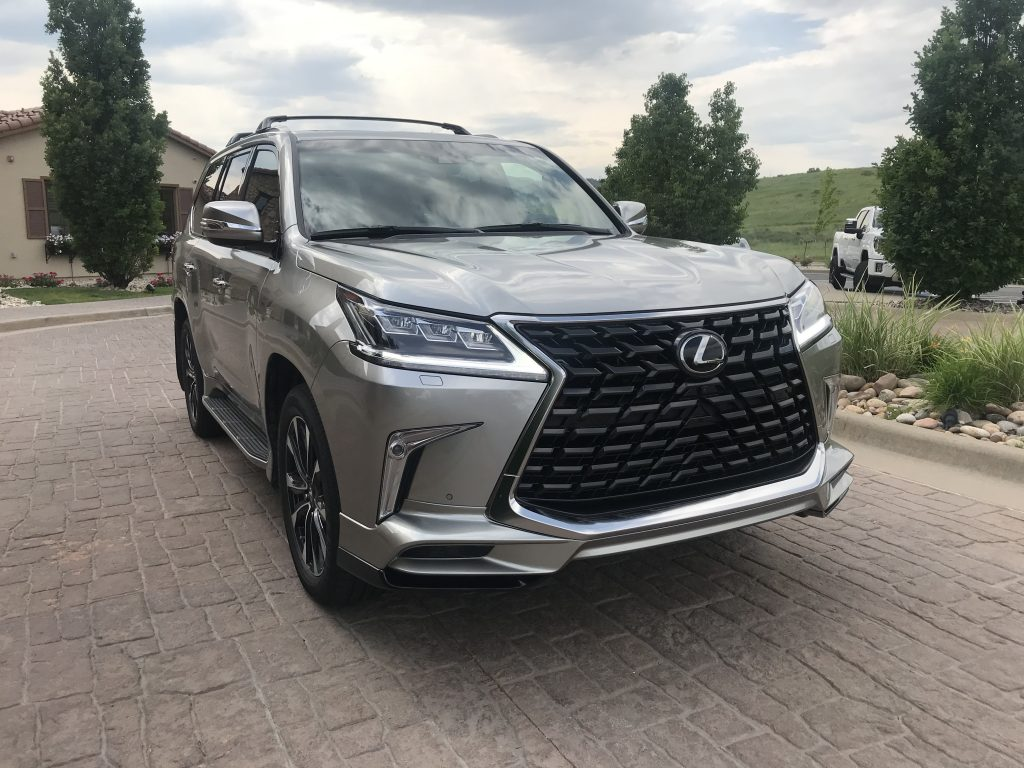 Front three-quarter shot of the 2021 Lexus LX 570 as it sits in a parking lot driveway for our full review.