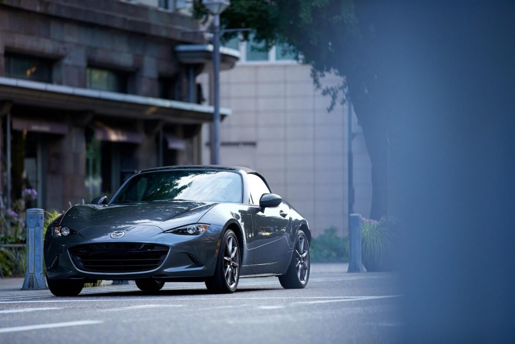 A 2021 Mazda MX-5 Miata  parked downtown, the Miata is an affordable new sporty car