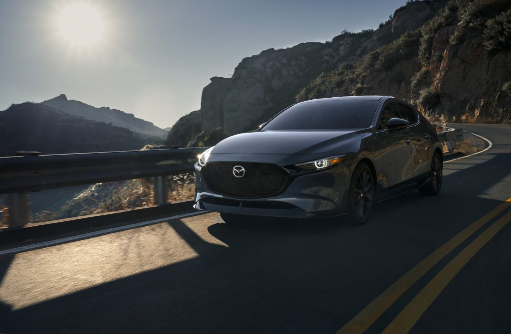 A dark blue 2021 MAZDA3 driving, the new Mazda3 is the best affordable AWD car on U.S. News' list