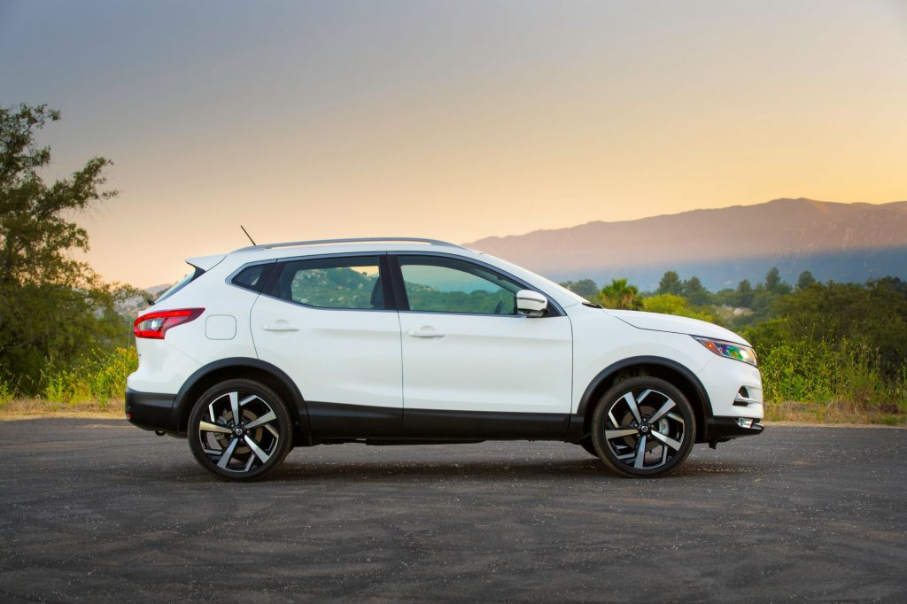 A white side-view of the 2021 Nissan Rogue on a blacktopped area with a background of a clear sunset with hills and trees.