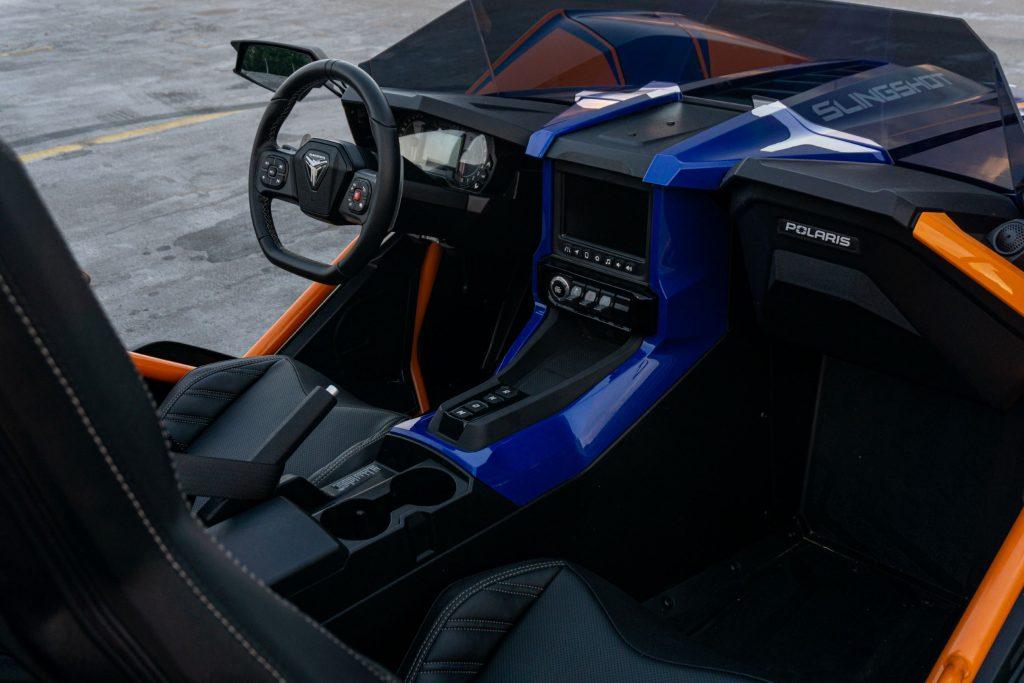 The black cockpit of a blue-and-orange 2021 Polaris Slingshot R
