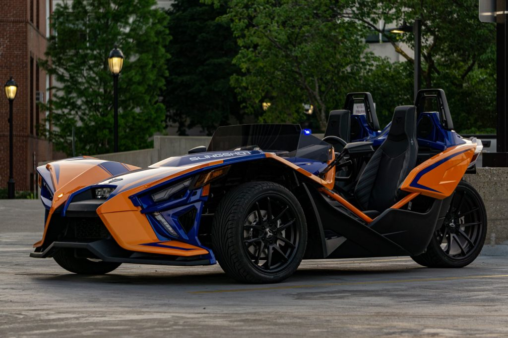 The front 3/4 view of an orange-and-blue 2021 Polaris Slingshot R in a parking lot
