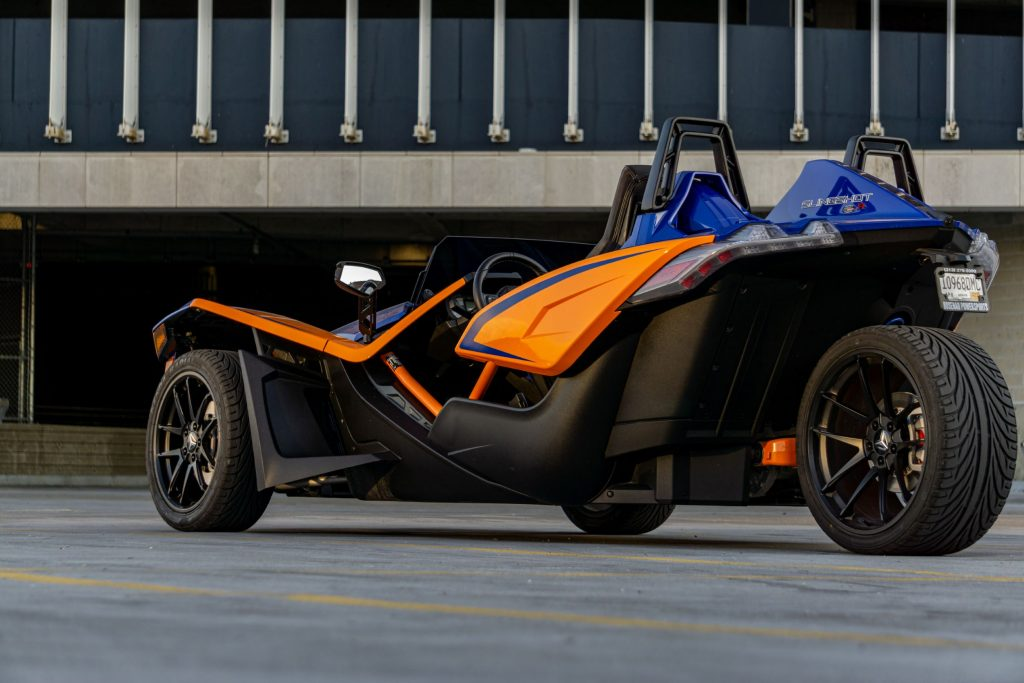 The rear 3/4 view of a blue-and-orange 2021 Polaris Slingshot R in a parking lot