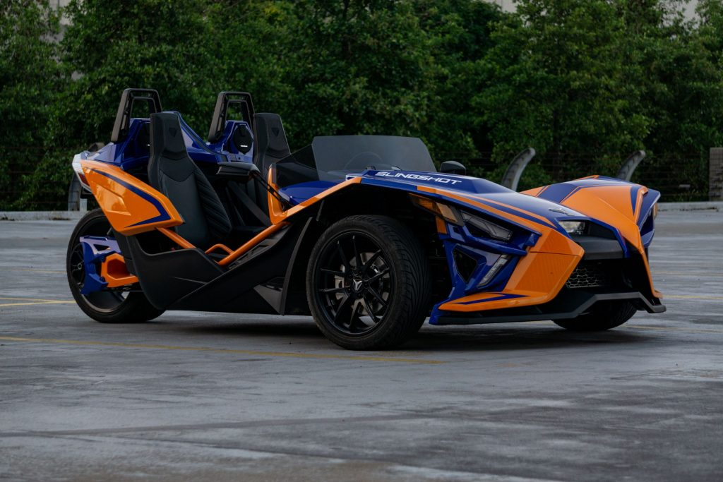 The side 3/4 view of a blue-and-orange 2021 Polaris Slingshot R in a parking lot