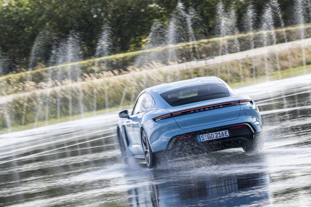 A sky-blue 2021 Porsche Taycan 4S maneuvers on wet pavement as water shoots into the air