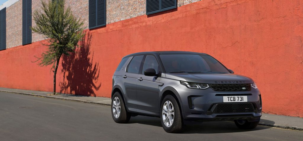 A grey 2021 Range Rover Evoque sits in front of a orange and grey brick building with two windows on a blacktop road.