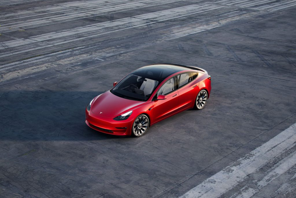 An overhead shot of a red 2021 Tesla Model 3 parked on an empty air strip