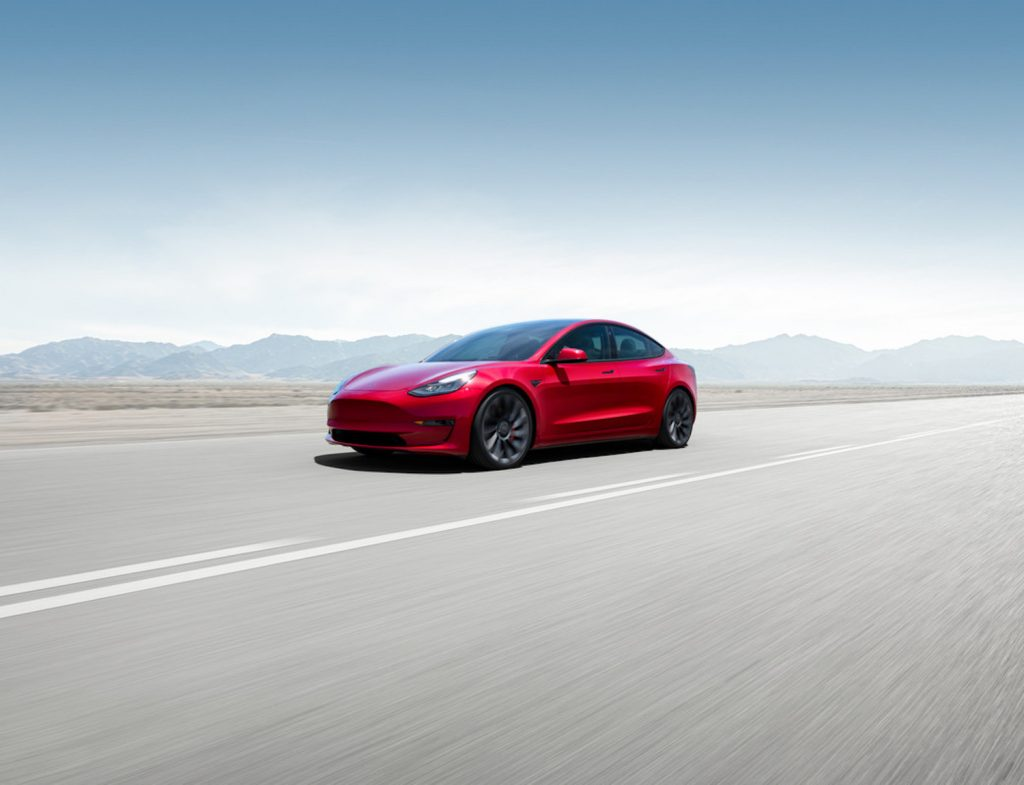 A red 2021 Tesla Model 3 driving through the mountains with a blue sky above it, the 2021 Tesla Model 3 is one of the best AWD cars of 2021