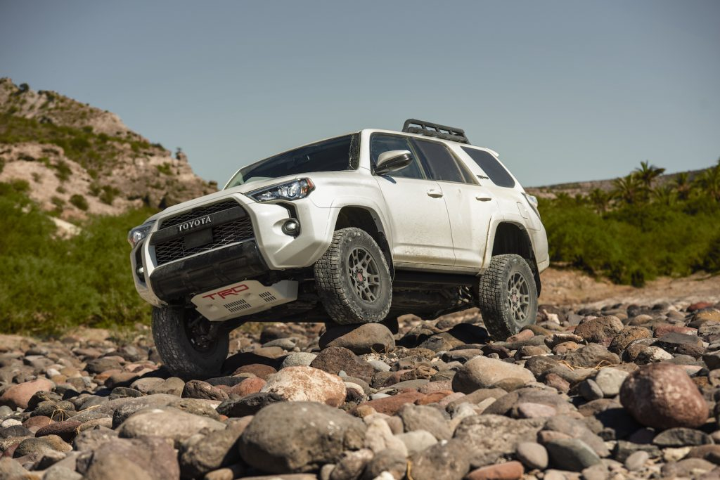 A white 2021 Toyota 4Runner TRD Pro crawling over rocks