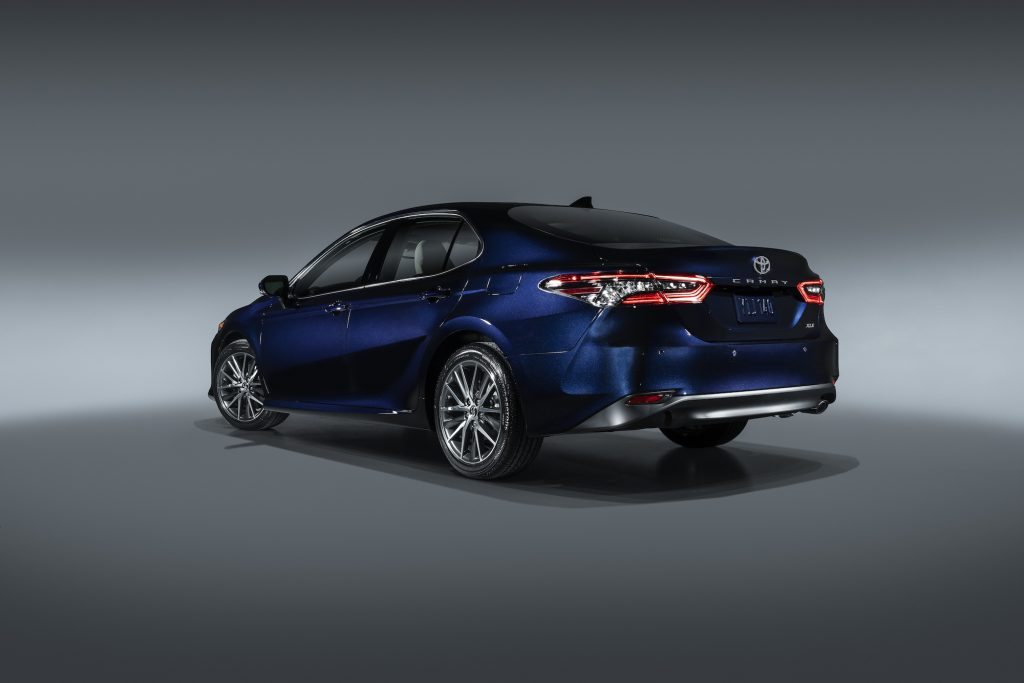 A deep-blue metallic 2021 Toyota Camry midsize sedan parked in a studio with a gray backdrop