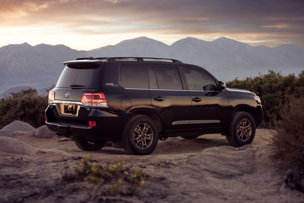 A 2021 Toyota Land Cruiser SUV parked on a rocky plain as the sun sets over a mountain range