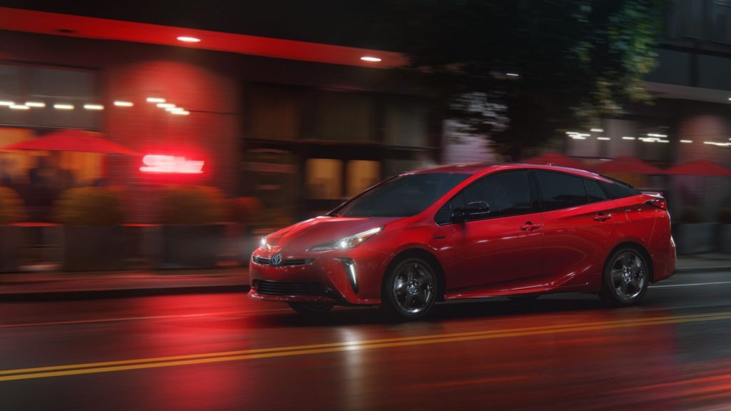 A 2021 Toyota Prius hybrid hatchback driving through a city at night