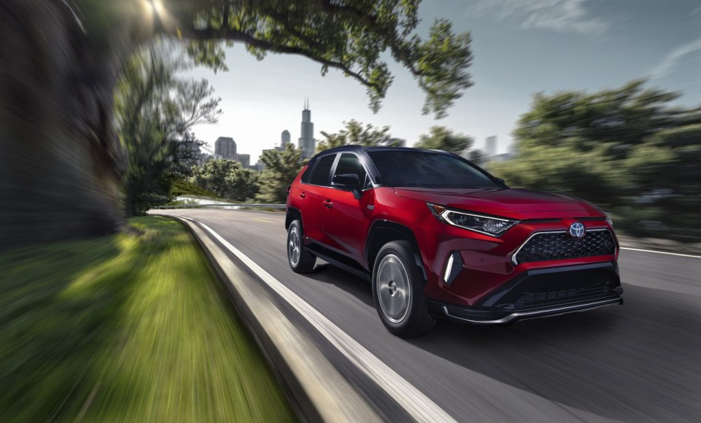 A red 2021 Toyota RAV4 Prime plug-in hybrid compact SUV traveling on a road away from a city