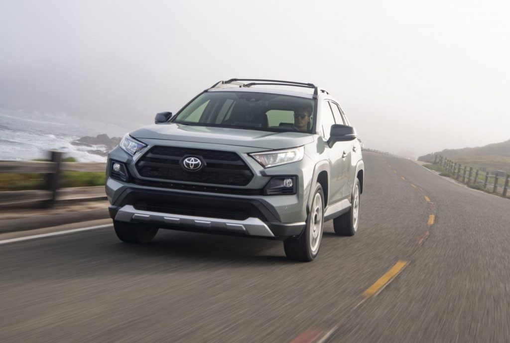 A silver 2021 Toyota RAV4 driving on a highway next to the ocean.