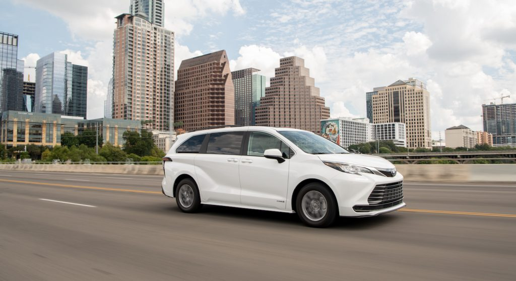A white 2021 Toyota Sienna driving in the city