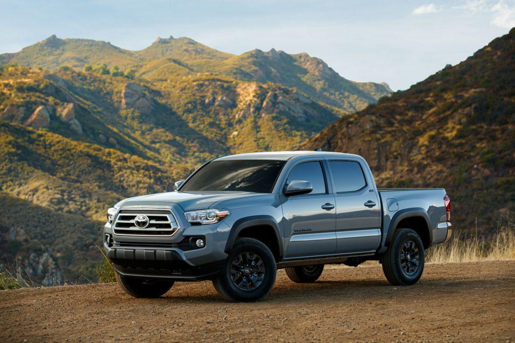A silver 2021 Toyota Tacoma midsize truck in a desert mountainous area.