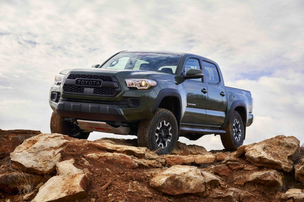 A dark green 2021 Toyota Tacoma sitting on top of a brown rocky terrain with a cloud covered background.