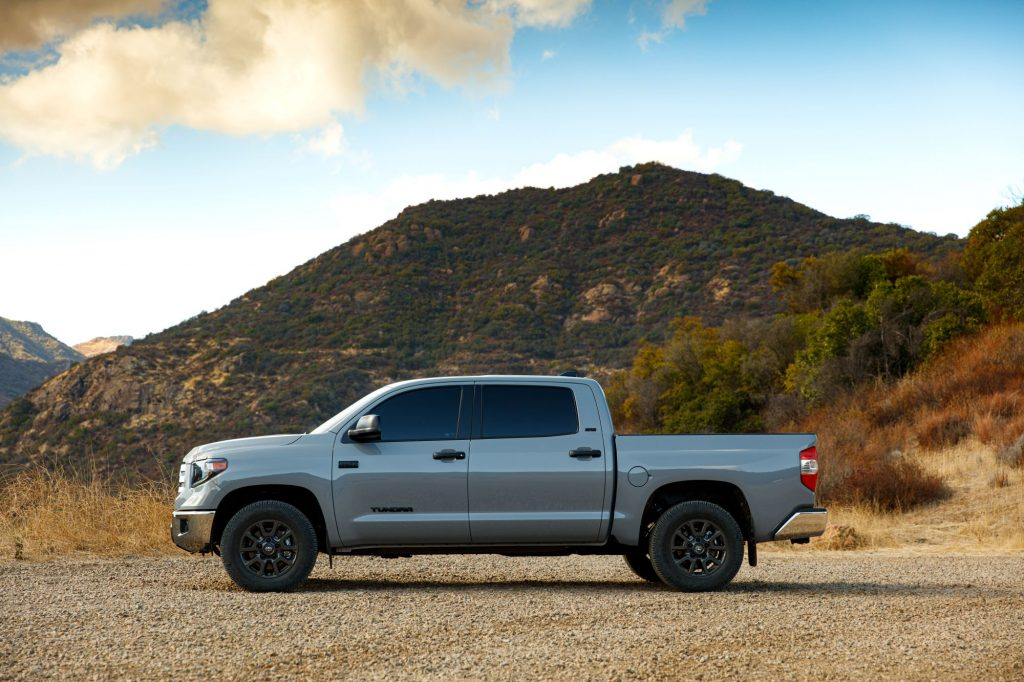 A 2021 Toyota Tundra Trail Edition gray pickup truck model parked on a dirt road near a grassy mountain
