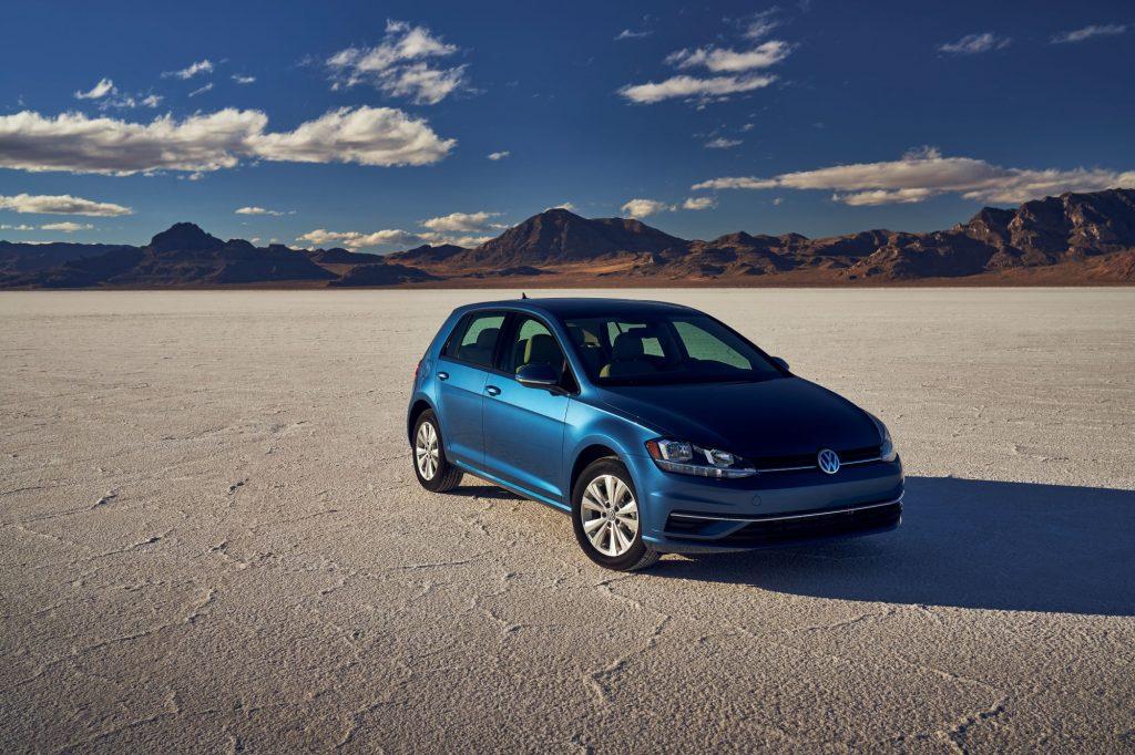 A blue 2021 Volkswagen Golf hatchback parked on a desert plain near a mountain range