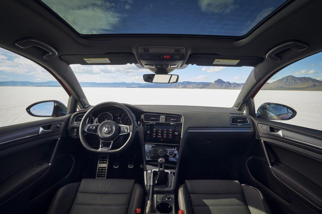 The black interior of a 2021 Volkswagen Golf GTI hatchback parked in a desert