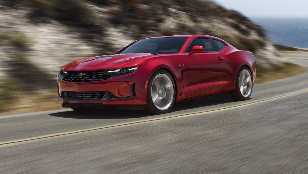 A red 2021 Chevy Camaro racing down the road
