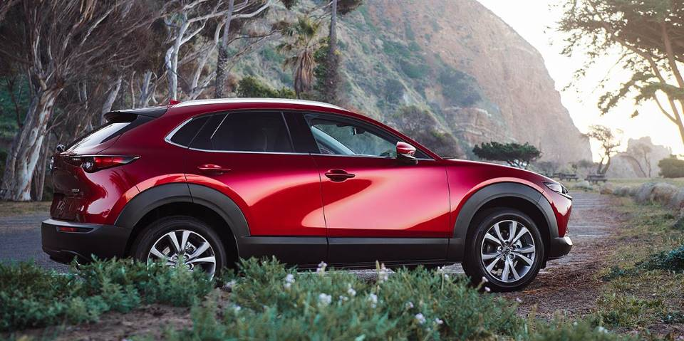 A red 2021 Mazda CX-30 in the woods.