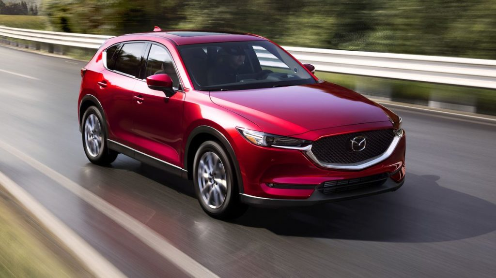 a red 2021 Mazda CX-5 driving on the road at speed