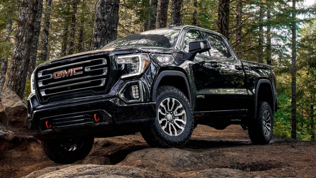 A black 2021 GMC Sierra AT4 off-roading in the woods