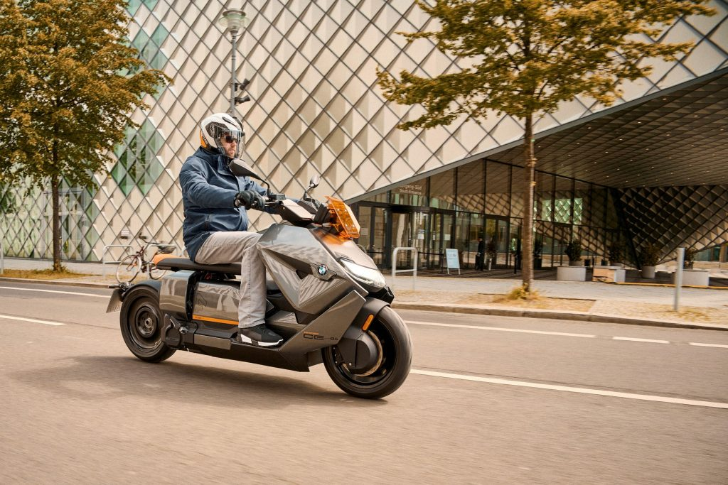 A blue-and-gray-clad rider on a gray-and-orange 2022 BMW CE 04 on a city street