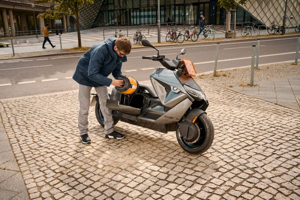 A blue-and-gray-clad rider retrieves their helmet from the under-seat storage compartment of a parked gray-and-orange 2022 BMW CE 04